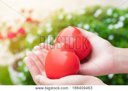 Teen hand's holding red heart balls in nature background care and valentine concept.