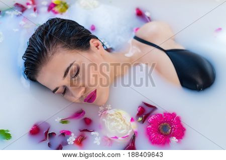Closeup view of Woman in bath. Sexy brunette woman relaxing in hot milk bathtube with flowers. she is wearing black sexual lingerie. Spa satisfaction