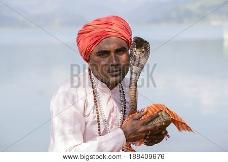 POKHARA NEPAL - OCTOBER 07 2016 : Portrait of snake charmer adult man in turban and cobra sitting near the lake