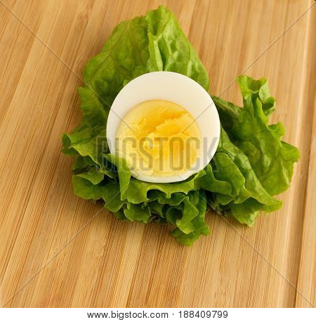 Sliced boiled egg and lettuce leaf. Egg cut in a half.