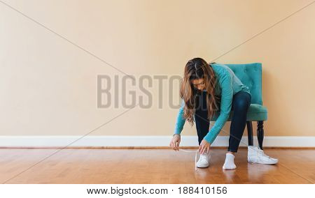 Young Latina Woman Tying Her Shoes