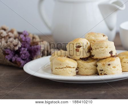 Homemade raisin scones serve with homemade strawberries jam,clotted cream and tea.Scones is English pastry for afternoon tea,cream tea.Delicious scones Devon shire or Cornish cream style. Scones in natural tone concept.