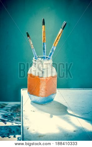 Brushes for painting stand with bristles up in a glass