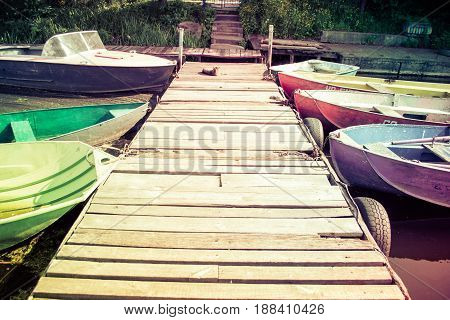 Wooden old berth. There are several boats on the dock. Sunny warm day