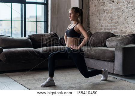 Pretty fit woman doing frontal lunges or squat exercise indoors in a flat.