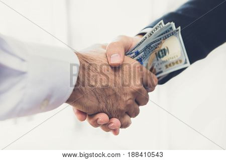 Businessmen making handshake with money in hands - bribery corruption and venality concepts