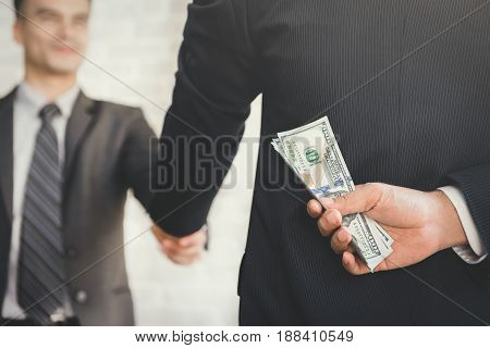 Businessmen making handshake with hidden money at the back - bribery and corruption concepts