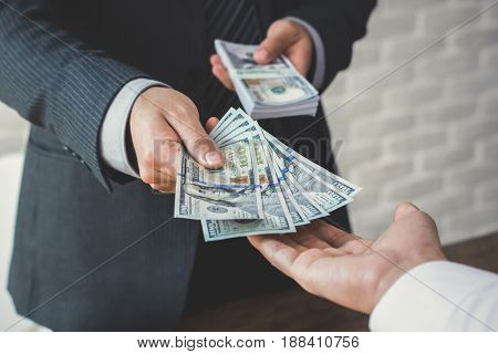 Businessman giving or paying money to a man US dollar bills - loanbribery and financial concepts