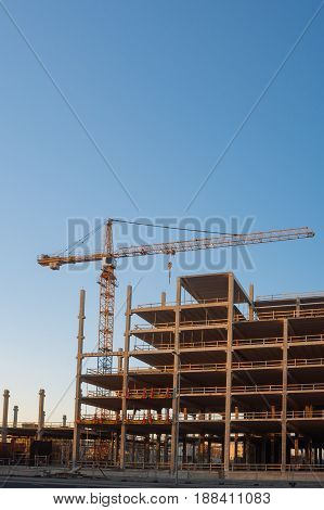 Crane at construction site by the morning vertical composition. Building development concept