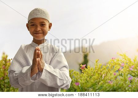 Asian muslim kid smiling and greeting at garden