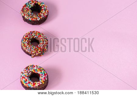 Three Baked Chocolate Doughnuts With Chocolate Glaze With Confetti Over Pink Background. Overhead Vi