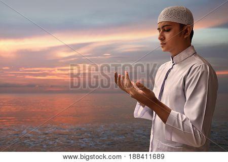 Muslim man praying to god on the beach