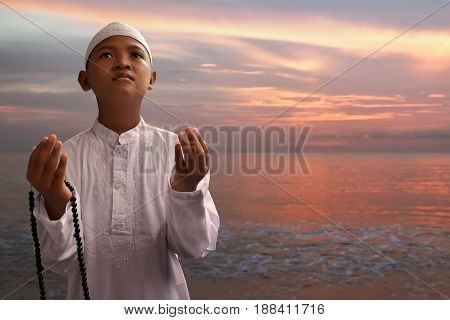 Asian muslim kid praying to god on the beach