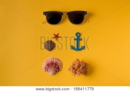 Summer background composition: From above shot of sunglasses composed with seashells on yellow. Top view. Flay lay.