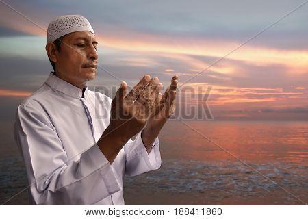 Old muslim man praying to god on the beach