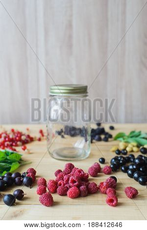 Red white black currant red and black raspberries white strawberries and mint leaves with glass jar on wooden table as ingredient to healthy cocktail beverage yogurt smoothie