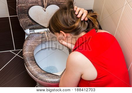 Woman Vomiting Into The Toilet Bowl In Bathroom