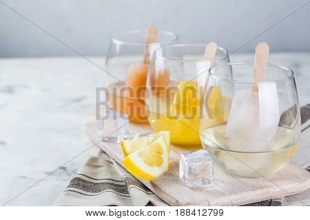 Colorful ice popsicles with wine in glasses, rustic wood background