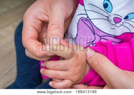 Woman Applying Plaster Around Finger Of Little Girl