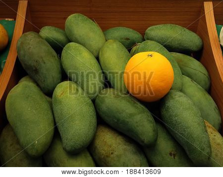 The Only Orange Among a Pile of Mangoes