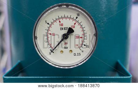 Presure gauge / gage in stall in a pressured tank of an air pump machine; close up