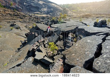 Young Female Tourist Exploring Surface Of The Kilauea Iki Volcano Crater With Crumbling Lava Rock In