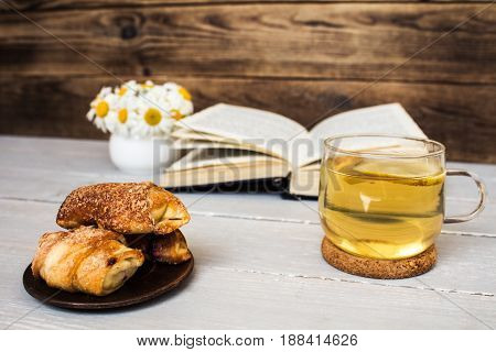 book and tea daisies croissants on wooden background