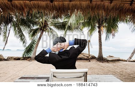 Businessman relaxing at the beach in summer