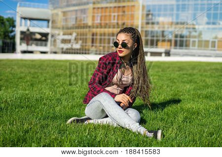 Young beautiful girl with zizi cornrows dreadlocks listening to music sitting on the lawn. She is dancing