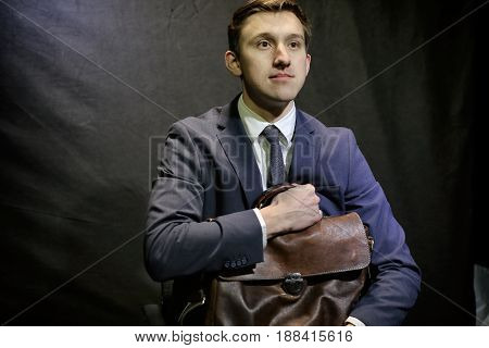 Young man in dark blue business suit sits with suitcase.