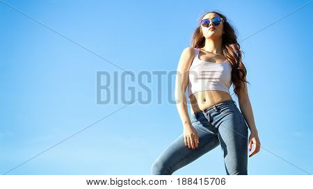 Beautiful Young Woman over blue Sky. Fashion poses