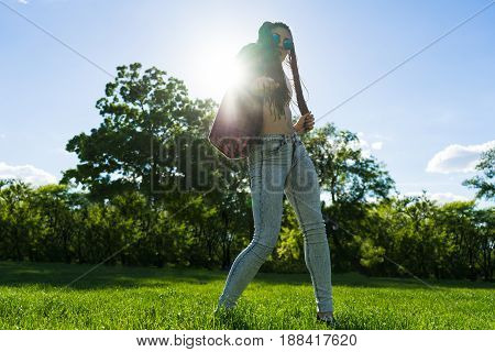 carefree girl with zizi cornrows dreadlocks dancing in the sunset on green grass of lawn