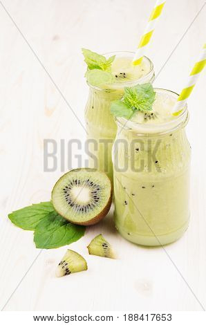 Freshly blended green kiwi fruit smoothie in glass jars with straw mint leaf cute ripe berry close up. White wooden board background vertical.