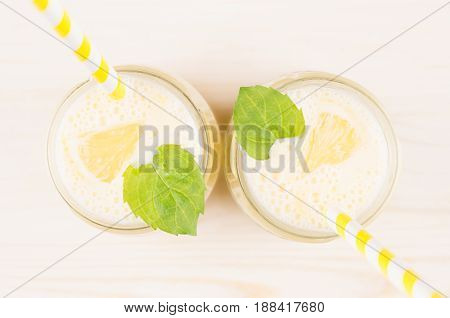 Freshly blended yellow lemon smoothie in glass jars with straw mint leaf cut lemon top view close up. White wooden board background.