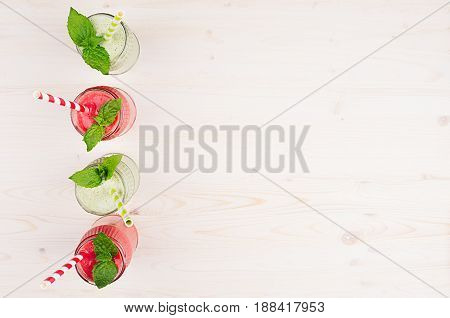 Freshly blended green and red fruit smoothie of strawberry and apple in glass jars with straw mint leafs top view. White wooden board background copy space.