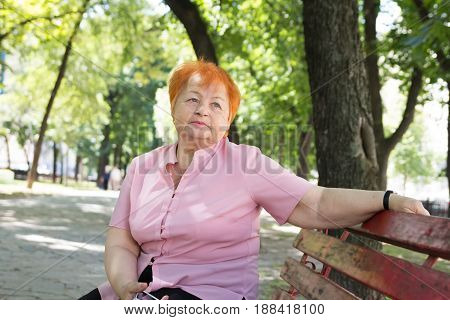 Elegantly dressed elderly woman is sitting on a bench in a city park.