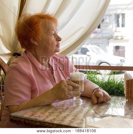 elegantly dressed elderly woman drinks coffee in outdoor cafe. Summer. City.