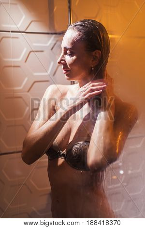 Sexy blonde in the shower touching her hair.