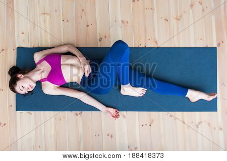Top view of pretty skinny young Caucasian woman wearing sportswear lying on mat relaxing after workout in gym.