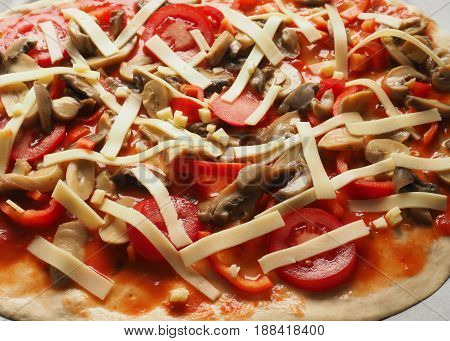 Prepared unbaked pizza with tomatoes paprika and mushrooms close up shot