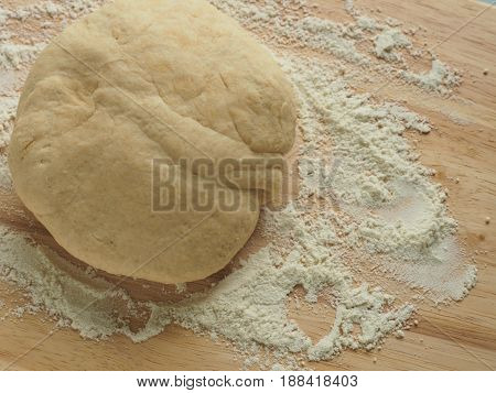 Pizza dough on a wooden cutting board in a kitchen