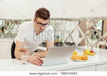 Young bearded businessman wearing white T-shirt, using laptop. Man checks email on computer. Freelancer working outside office