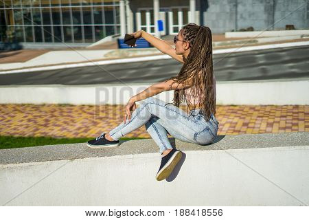 Afro girl with zizi cornrows dreadlocks shooting selfie on her smartphone. Urban street style