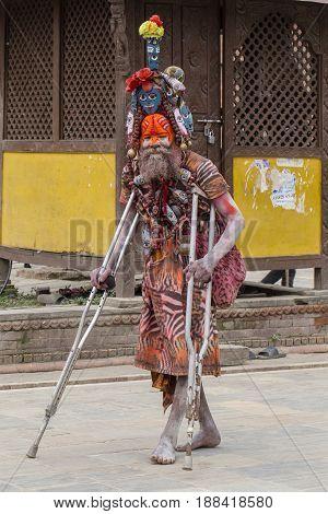 KATHMANDU NEPAL - SEPTEMBER 29 2016 : Sadhu holy man patient on crutches in Pashupatinath Temple Kathmandu Nepal