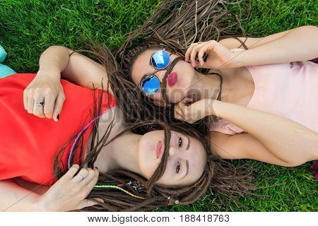 Two girl friends with zizi cornrows dreadlocks lying on green lawn and they Imitate the mustache with dreadlocks.
