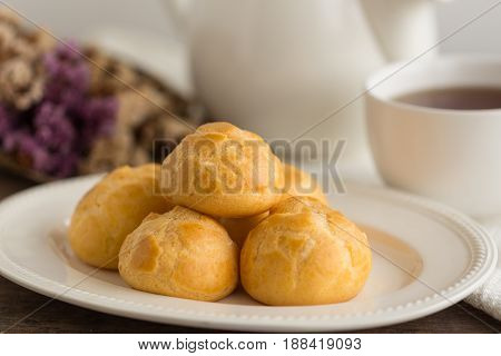 Homemade cream puffs or eclaires filled with vanilla custard cream. Golden choux cream on white plate put on rustic wood table. Cream puffs serve with tea in white pot or cup of coffee. Cream puffs or choux cream or eclairs. French pastry : cream puffs or