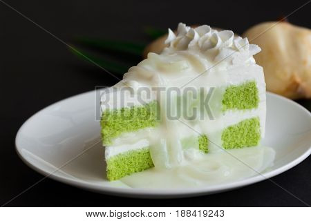 Pandan cake frosting with whipped cream topping with young toddy palm seed in coconut milk sauce. Pandan cake on white plate put on granite table. Thai style dessert : pandan cake. Delicious Thai style cake.