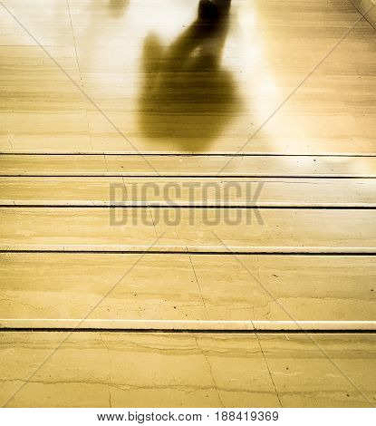 Man silhouette walking through the exit at the end of the stairs
