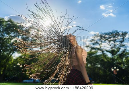 carefree girl with zizi cornrows dreadlocks with hair up into air dancing in the sunset on green grass of lawn. Sunlight through hair