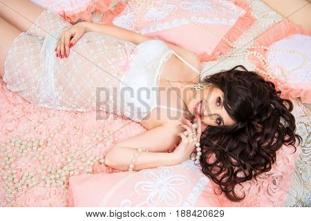 Smiling beautiful pregnant brunette girl in soft peach pillows.
